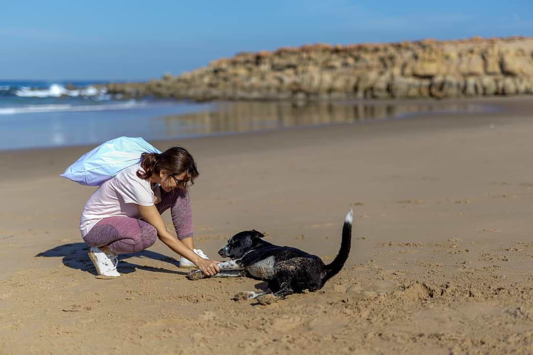 Frau sammelt Müll am Strand
