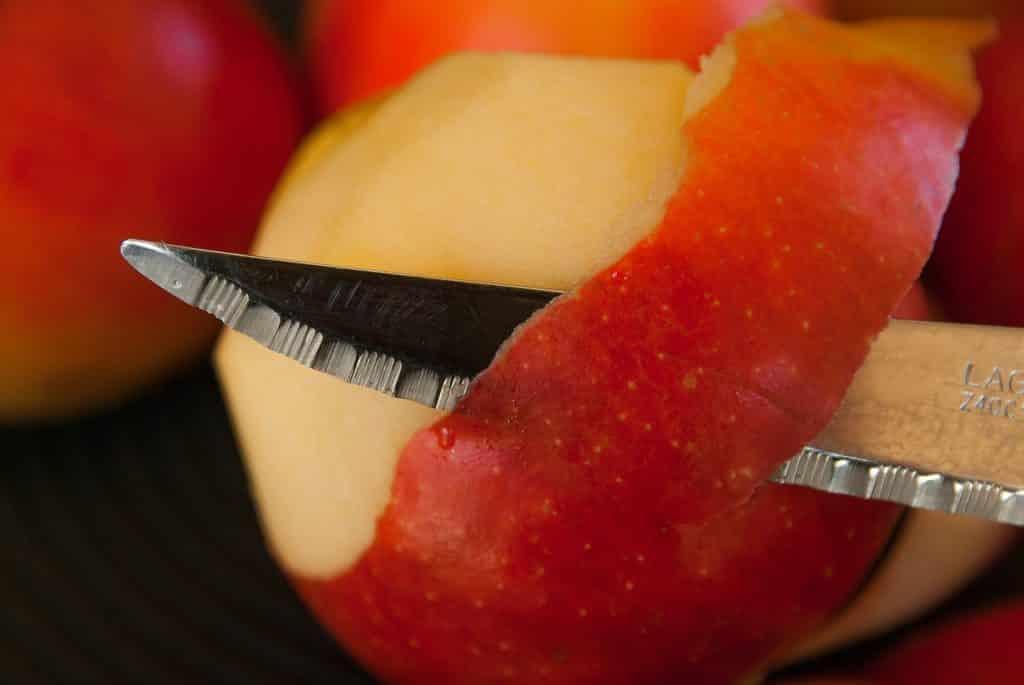 ein roter Apfel wird geschält